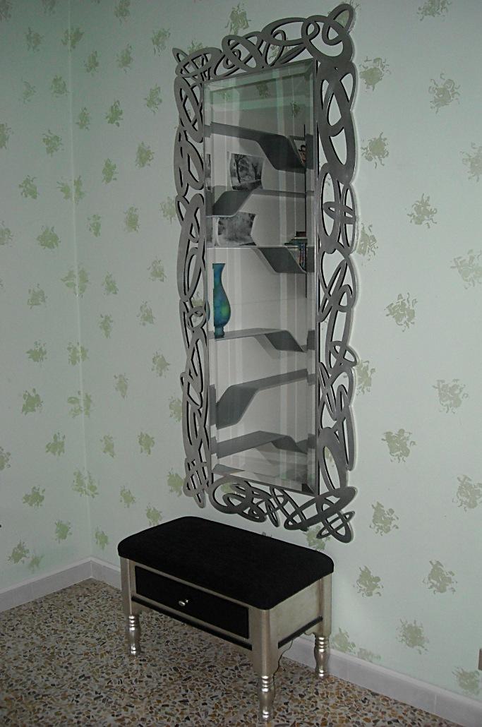 Specchio con cornice traforata e rifinita foglia argento.