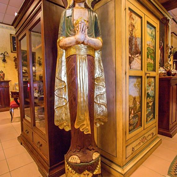 Buddha in legno , in piedi con mani giunte raffigura il gesto di adorazione e di saluto.