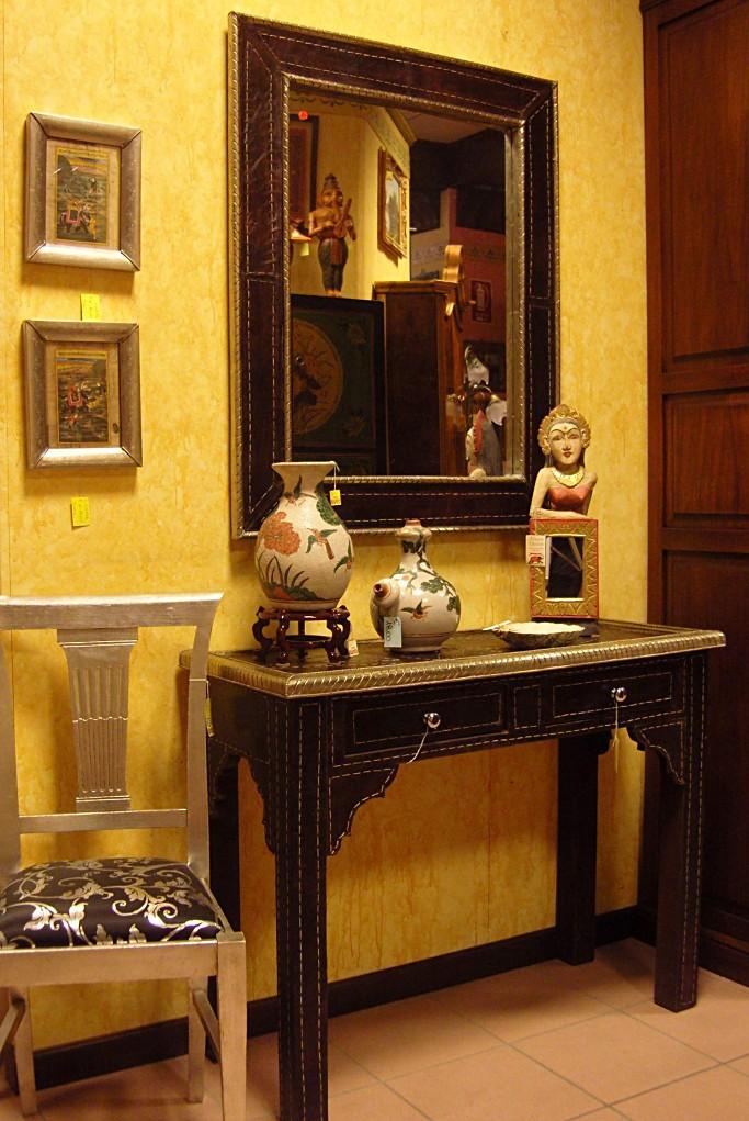 Consolle e specchio Indiano, in legno foderato di pelle color testa di moro e bordi in lamina argentata.